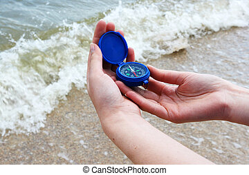 Dark blue compass in hands