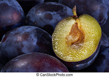 Dark blue ripe fleshy plums-one from them is cut half and expires with sweet juice