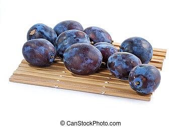 Dark blue ripe fleshy plums-one from them is cut half and ...