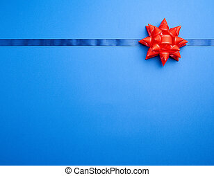 dark blue silk ribbon and a large knotted red bow on a blue background
