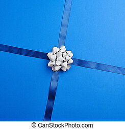 dark blue silk ribbon crossed on a blue background in the middle of a gray bow
