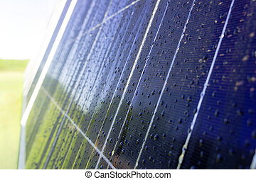 Dark blue solar panel with dew drops and reflection of green trees on the background of green grass and blue sky