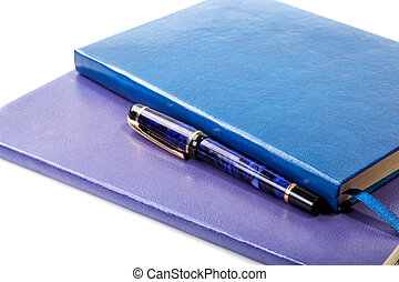 Dark blue writing-books and fountain pen isolated on a white background