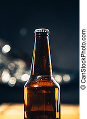 dark bottle of beer on a blurred background