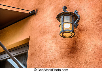 Dark brown outside lighting fixture against a stone wall.