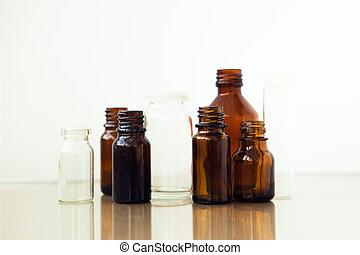 Dark brown phials on white background. Small empty bottles.