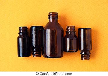 Dark brown phials on yellow background. Small empty bottles