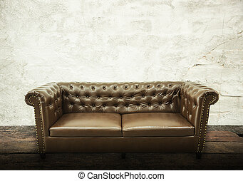 Dark brown vintage beautiful luxurious vintage sofa interior with gray concrete texture wall in room.Fashion concept, relaxation concept with free space for text advertising.Vintage retro background.
