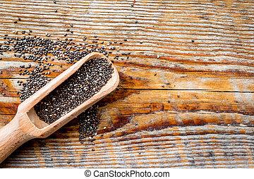 Dark chia seeds in wooden scoop on wooden background top view copyspace