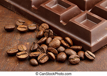 dark chocolate bar and coffee beans on wooden table