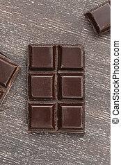 Dark chocolate bar on a wooden table