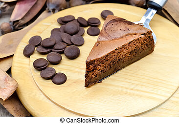 Dark chocolate cake on wooden plate