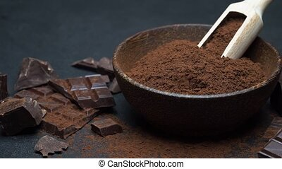Dark Chocolate chunks and cocoa powder in wooden bowl on...