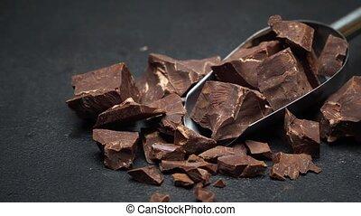Dark Chocolate chunks in metal scoop on dark concrete...