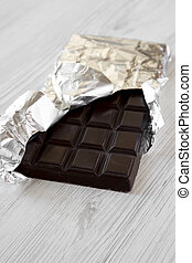 Dark chocolate in a wrapper over white wooden background, side view.