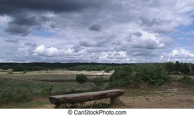Dark clouds above a vacant bench in Veluwe National Park THE...