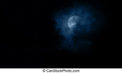 Night sky with large clouds moving across the moon