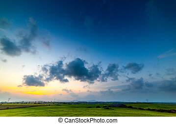 Dark clouds over a green field at sunset