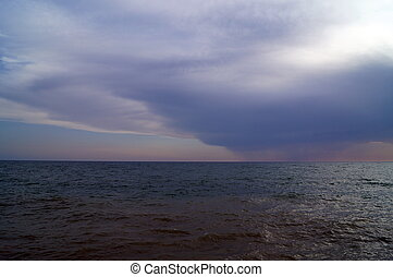 Dark clouds over the sea at sunset