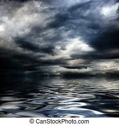 dark cloudy stormy sky with clouds and waves in the sea