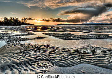Dark dramatic rippled beach sunset - Rippled sand and water...