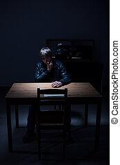 Dark empty room - Arrested man sitting in dark empty room