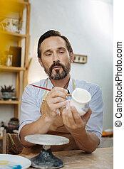 Dark-eyed bearded ceramist wearing apron and working -...