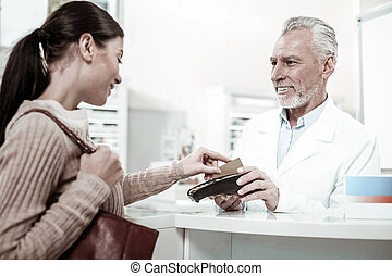 Dark-eyed bearded pharmacist holding pin pad while client paying for order by card