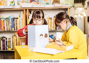Dark-eyed sunny child wearing red sweater looking at interesting book