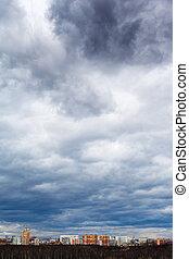 dark gray storm rainy clouds under city