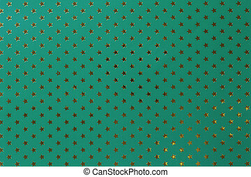Dark green background from metal foil paper with a golden stars pattern.