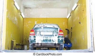 Dark green car is washed by two employees