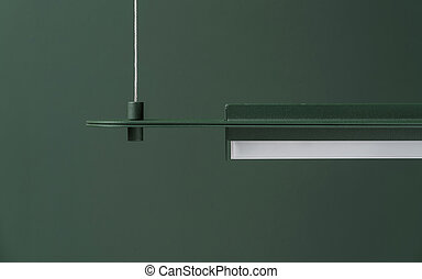 Dark green metal lamp hanging on colorful wall background in studio
