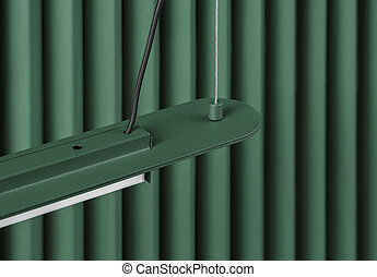 Dark green metal lamp hanging on folded colorful wall background in studio