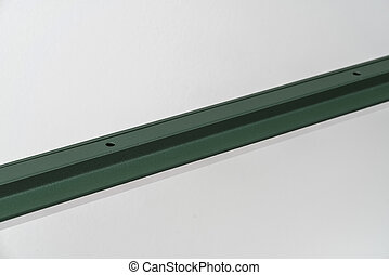 Dark green metal lamp hanging on gray wall background in studio