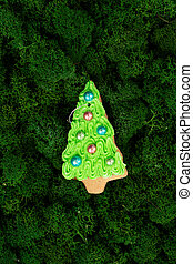 Christmas tree gingerbread cookie on dark green moss background