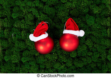 Pair of Christmas balls in hats on dark green moss background