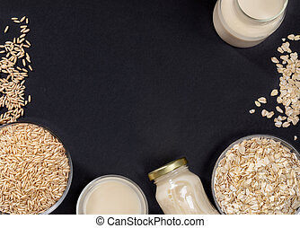 Dark grey background with frame of glass bowls with oat seeds and flakes and glass containers with oat milk.