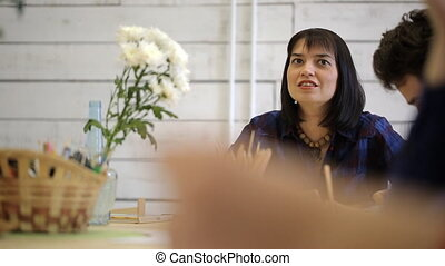 Dark-haired and black-eyed woman sits at table, holds pencil and talks.