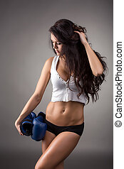 Dark-haired athlete posing with boxing gloves