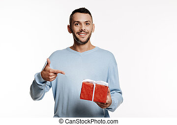 Dark-haired bristled man pointing at gift box