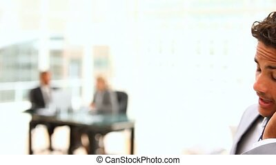 Dark-haired businessman speaking on the phone with business...