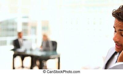 Dark-haired businessman speaking on