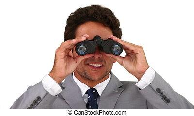 Dark-haired businessman using a pair of binoculars
