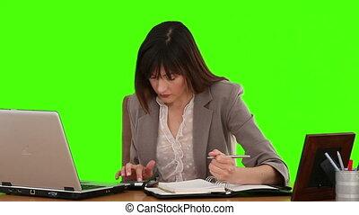 Dark-haired businesswoman calculating her bills at her desk