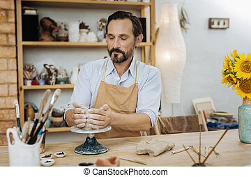 Dark-haired ceramist feeling satisfied during the process of...