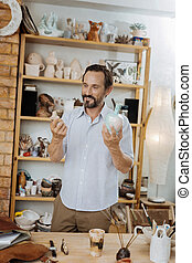 Dark-haired ceramist standing near shelve stand with his...