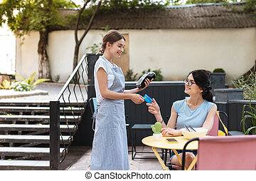 Dark-haired client of restaurant paying for her tasty lunch