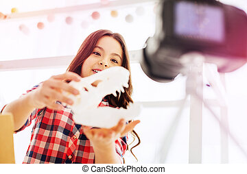 Dark-haired cute schoolgirl playing tricks in front of camera filming blog