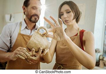 Dark-haired female ceramist improving her future tea cup -...